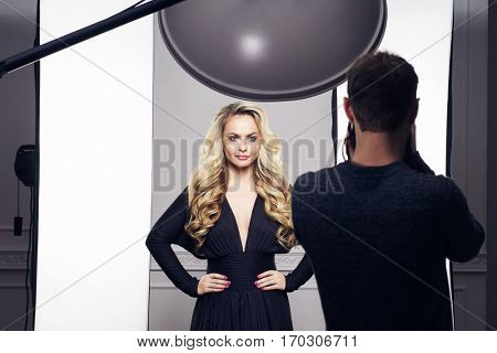 Photographer taking pictures of an attractive and beautiful model. Backstage shooting. Fashion, beauty, glamour concept.