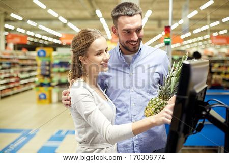 shopping, food, sale, consumerism and people concept - happy couple buying pineapple at grocery store or supermarket self-service cash register