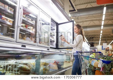 sale, food, consumerism and people concept - woman with shopping cart choosing ice cream at grocery store freezer
