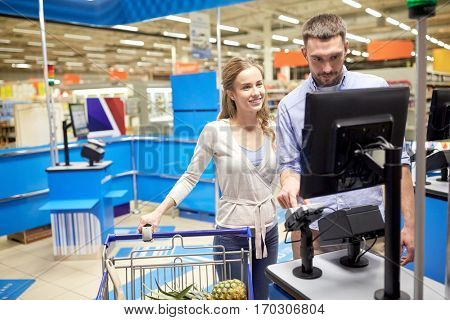 shopping, sale, consumerism and people concept - happy couple buying food and entering pin code at grocery store or supermarket self-service cash register