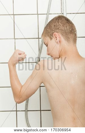 Little Boy Flexing His Biceps In The Shower