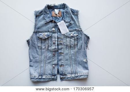 clothes, wear and fashion concept - denim vest or waistcoat with price tag on white background
