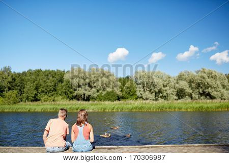 summer, vacation, love and people concept - happy teenage couple sitting on river berth looking at swimming ducks