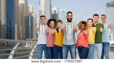 diversity, travel, tourism and people concept - international group of happy smiling men and women showing thumbs up over dubai city background