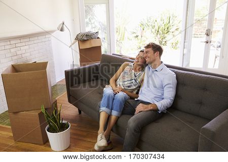 Couple Taking A Break On Sofa During Moving In Day