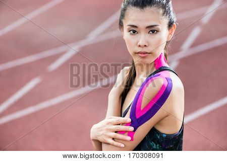 Woman taping with therapeutic tape on cinder track of sports stadium poster