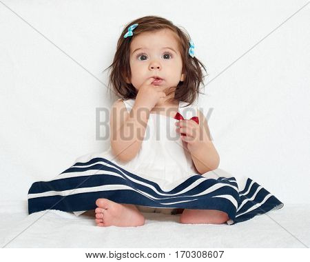 happy little child girl sit on white towel, happy emotion and face expression, very surprised, the finger in mouth