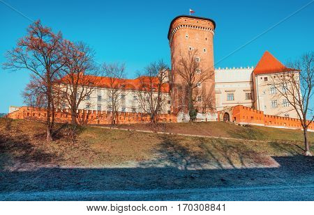 Wawel castle with brick tower. Landmark in Krakow old town. Poland. Winter morning landscape bright sunlight and trees long shadows.