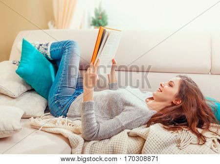 Pretty beautiful young girl reading a book. Lying at white sofa with wrap and pillows in modern interior room home. Sunny day warm light from window. Happy people lifestyle concept.