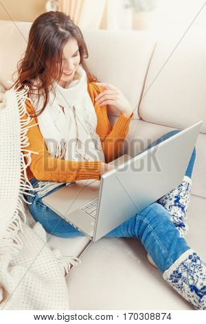 Young smiling girl with laptop sitting at white sofa warm plaid browsing new messages in online social networks. Internet browsing people