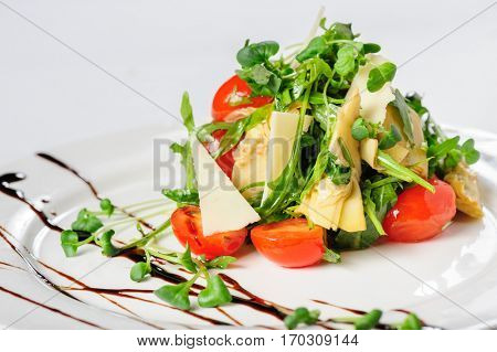 salad with artichoke, parmesan cheese, cherry tomato and green sprouts on white plate