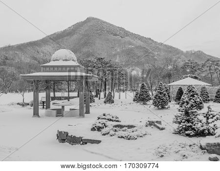 Winter landscape of a beautiful gazebo in a public park covered with soft white snow with mountain and overcast sky in the background