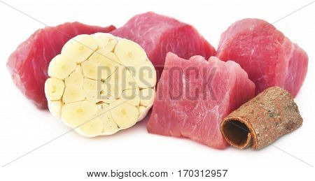 Raw beef with garlic and cinnamon over white background