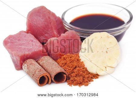 Raw beef with garlic and other spices over white background