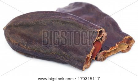 Closeup of Edible carob fruits over white background