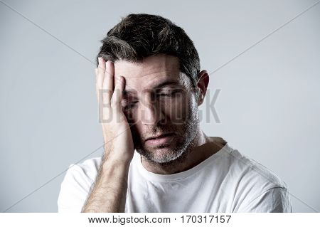 young attractive man with blue eyes sad and depressed looking lonely and suffering depression feeling sorrow and pain isolated on white background in sadness emotion concept