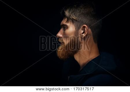 Close-up Image Of Serious Brutal Bearded Man On Dark Background