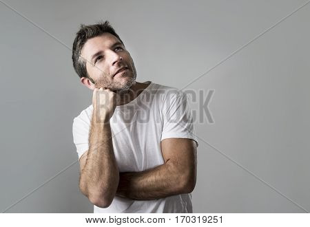 young attractive man gesturing thoughtful as if daydreaming for a future plan or project thinking isolated on grey background looking happy and satisfied