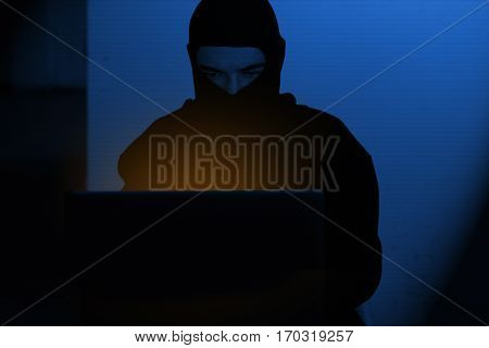 Hacker man in hoodie shirt typing hacking global netwok security on computer laptop over dark background with blue light
