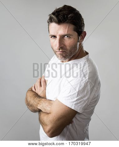close up portrait of young attractive man with blue eyes looking angry and mad in rage emotion and upset facial expression isolated on grey background posing with folded arms