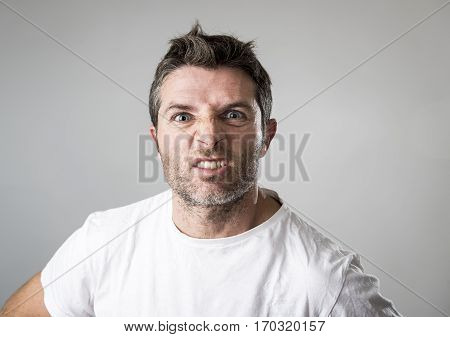 close up portrait of young attractive man with blue eyes looking angry and mad in rage emotion and upset facial expression isolated on grey background