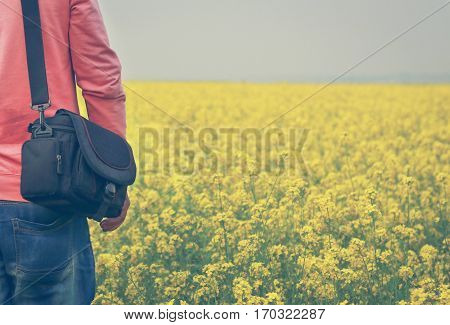 People with a black bag beside a mustard field in rural area of Bangladesh