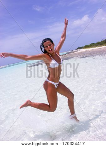 Latin woman running and jumping on caribbean beach.