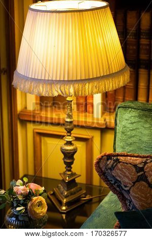 classic lamp on table by sofa - library in the background