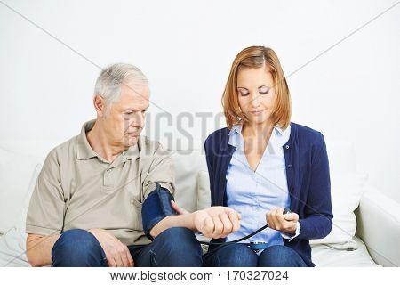 Nursing service doing blood pressure measurement for senior man