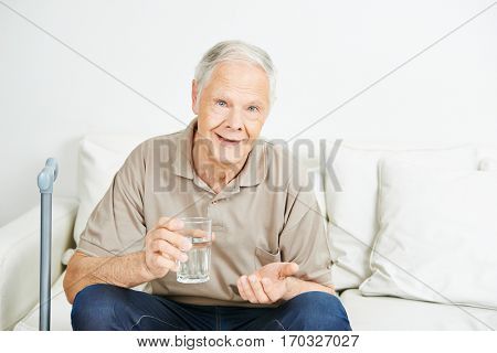 Old senior man swallowing medicine with a glass of water