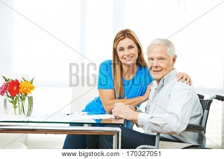 Woman and senior man filling out forms together at home
