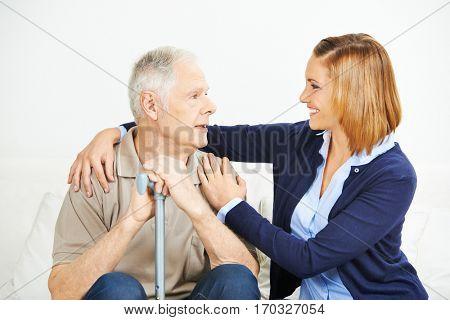 Adult daughter assisting senior man at home