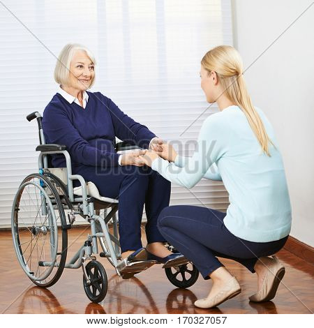 Young and old woman in wheelchair holding hands in a nursing home