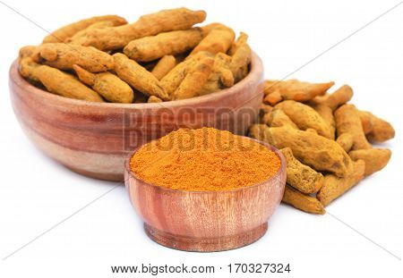 Whole and ground turmeric in bowl over white background