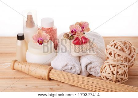 Spa still life on a wooden desk on a white background. Healthy lifestyle, body care, bathhouse, Spa treatment and relaxation concept. Bamboo massage stick, towel, moisturizing cream and other toiletry