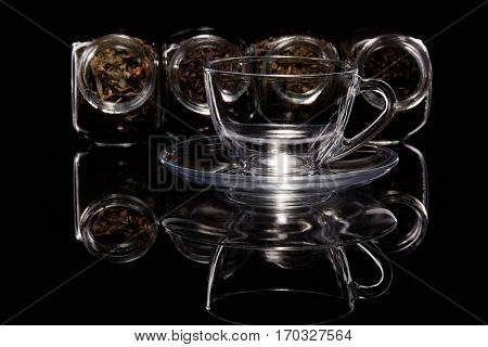 Various kinds of dry tea in glass jars and empty cup  standing on a black background.  Different kinds of tea leaves.