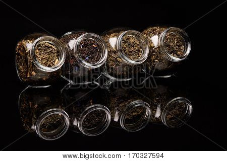 Various kinds of dry tea in glass jars standing on a black background.  Different kinds of tea leaves.