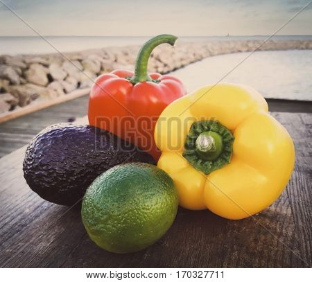 Two capsicums with lemon and avocado placed in a seashore