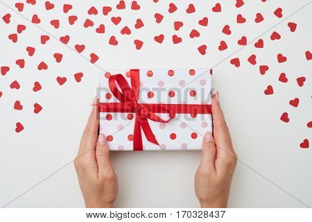 Top view of female hands holding small present box. Gift box on white background decorated with small carton hearts