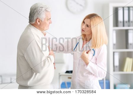 Aged patient complaining to doctor at hospital