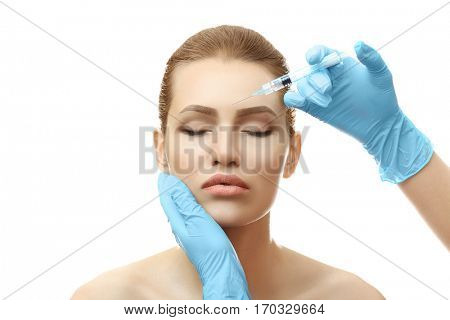 Young woman having cosmetic injection on white background. Plastic surgery concept