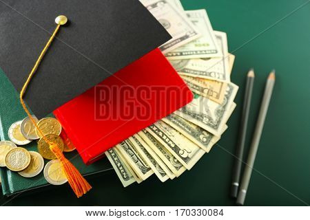 School supplies, graduation hat, dollar banknotes and coins on green background. Pocket money concept