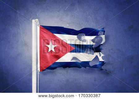 Torn flag of Cuba flying against grunge background.