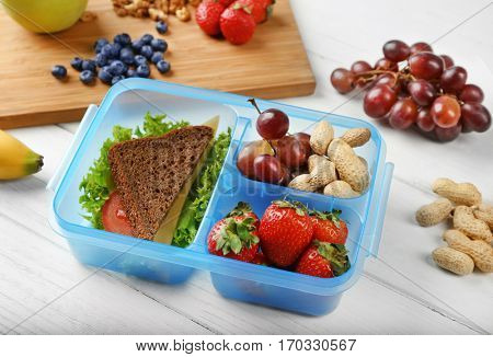 Lunchbox with sandwich and fruits on white wooden table