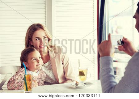 family, parenthood, technology and people concept - happy mother, father and little girl having dinner and taking picture by smartphone at restaurant