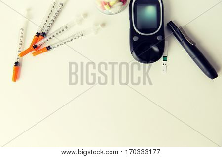 medicine, diabetes, advertisement and health care concept - close up of glucometer with blood sugar test stripe, insulin injection syringes and pills on table