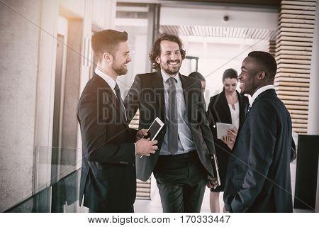 Happy businessmen having conversation in office