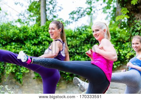 Three women doing kick boxing for warming up or having a power training in a forest