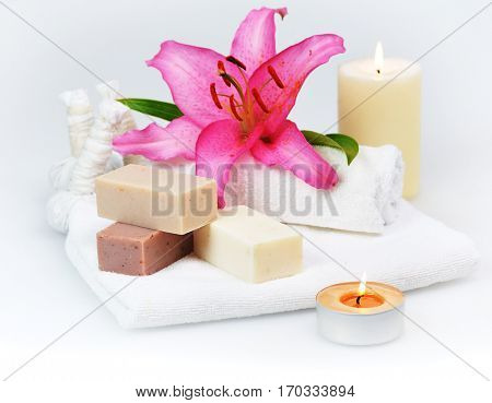 bars of herbal spa soap with white towels,candles and pink lily flower