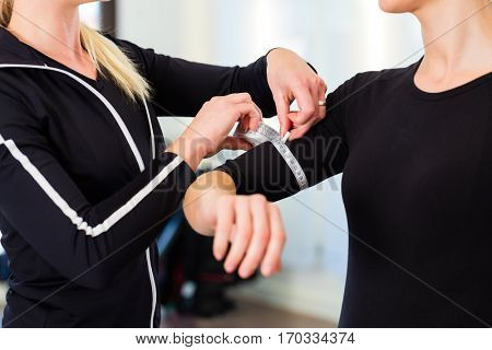 Female coach controlling muscle volume of woman after training in fitness studio with measure tape